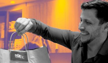Leonidas Munhoz sorrindo entregando sacola da empresa NozFit com grande crescimento em vendas