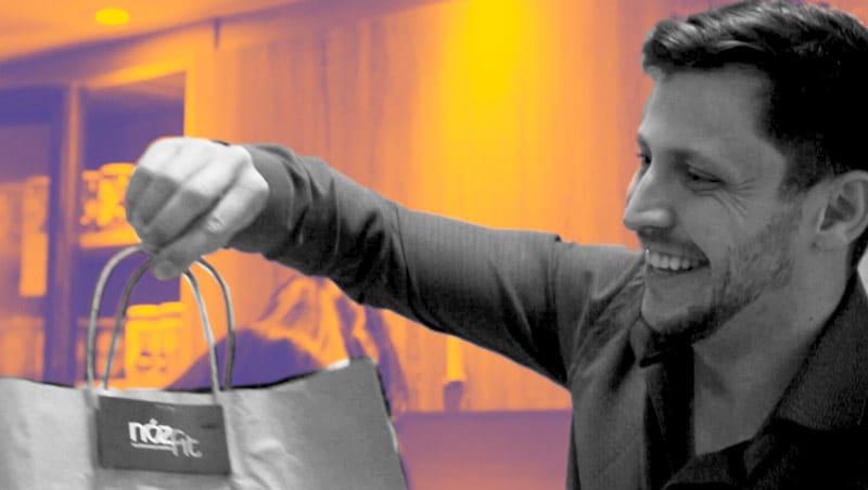 Leonidas Munhoz sorrindo entregando sacola da empresa NozFit